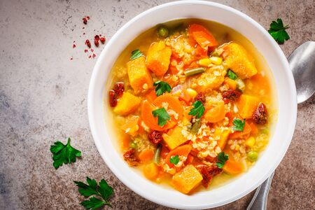 Vegetarian vegetable soup with lentils and pumpkin in a white plate. Healthy vegan food concept. Stock Photo - 133297113