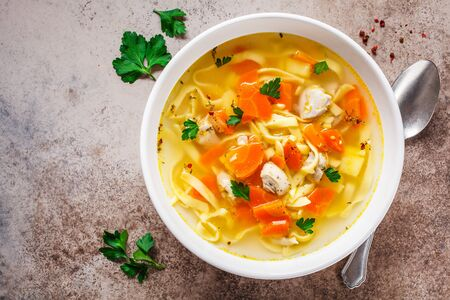 Chicken noodle soup with parsley and vegetables in a white plate, gray background. Stockfoto
