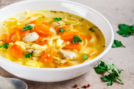 Zuppa di noodle di pollo con prezzemolo e verdure in un piatto bianco, sfondo grigio.