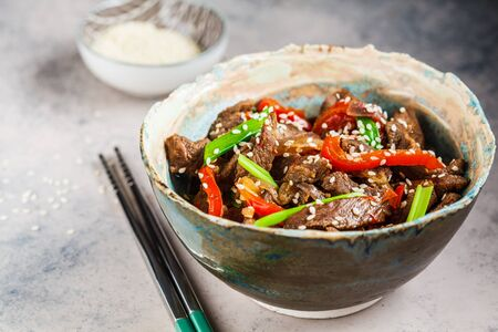 Asian teriyaki beef with green onions and sesame seeds in a beautiful bowl, grey background. Stockfoto