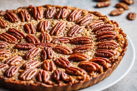 Whole pecan Pie on gray-brown background. Vegan dessert concept. Stock Photo