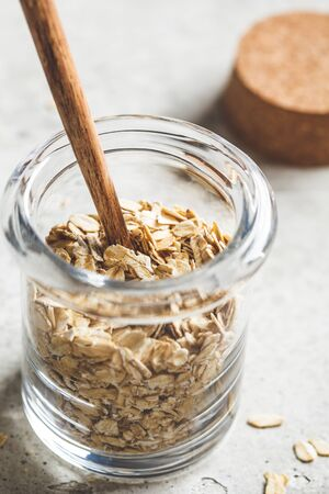 Raw oatmeal in a glass jar. Cooking food concept.
