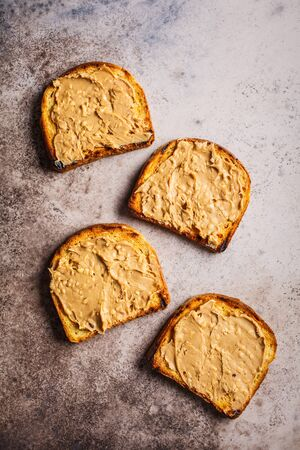 Crispy peanut butter toast on a gray background, top view, flat lay.