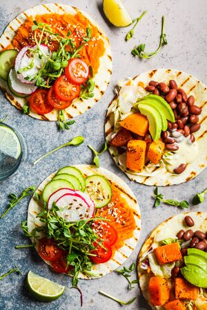 Open vegan tortilla wraps with sweet potato, beans, avocado, tomatoes, pumpkin and seedlings on a gray background, flat lay, top view. Healthy vegan food concept. Stockfoto