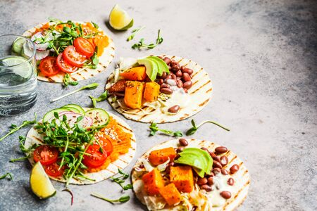 Open vegan tortilla wraps with sweet potato, beans, avocado, tomatoes, pumpkin and seedlings on a gray background, flat lay. Healthy vegan food concept.