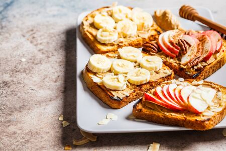 Peanut butter toast with banana and apple on a gray background, flat lay.