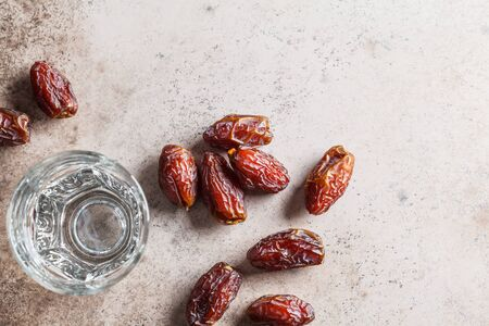 Dates and a glass of water, copy space, top view. Iftar food concept.