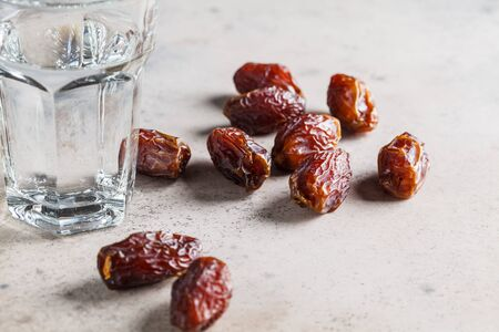 Dates and a glass of water, copy space. Iftar food concept. Stockfoto
