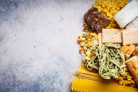 Various pasta background. Bread and different types of pasta on a gray-blue background, copy space.