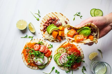 Open vegan tortilla wraps with sweet potato, beans, avocado, tomatoes, pumpkin and seedlings on a white background, top view, flat lay. Healthy vegan food concept.