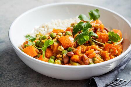 Veganes Curry mit Reis in einer weißen Schüssel. Curry mit Süßkartoffel, Erbsen und Bohnen in einem Teller mit Reis.