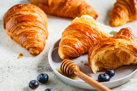 Fresh croissants with blueberries and honey, gray background, copy space.