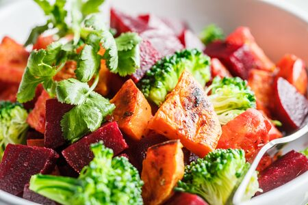 Baked sweet potato, beetroot and broccoli salad in a white bowl.