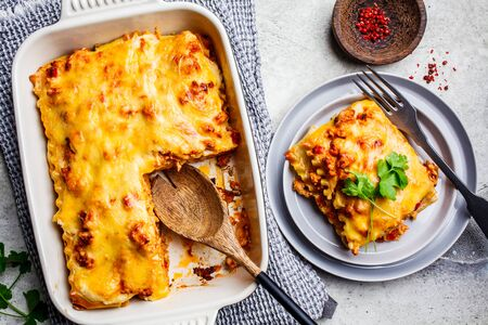 Classic meat lasagna with cheese on a light gray background, flat lay. Italian food concept.