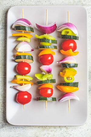 Cooking vegetable skewers on gray rectangular plate, top view. Vegan food concept.