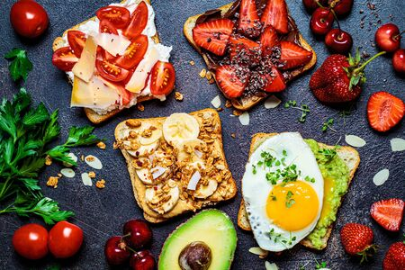 Breakfast different toasts with berries, cheese, egg and fruit, dark background. Zdjęcie Seryjne