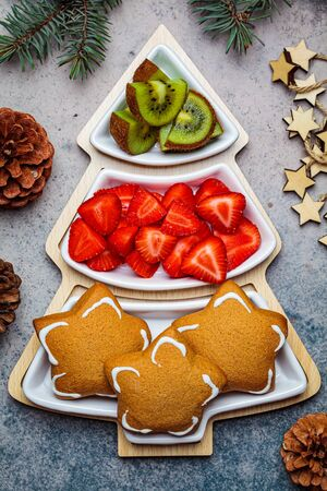 Holiday snacks - gingerbread, kiwi and strawberries on a plate Christmas tree. Zdjęcie Seryjne