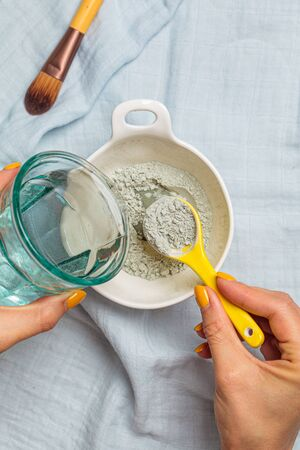 Preparing a clay face mask. Mixing dry clay with water. Skincare concept.