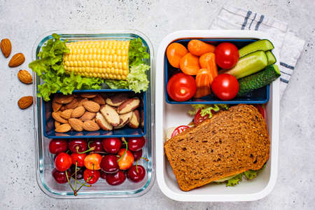 Lunch box with healthy fresh food. Sandwich, vegetables, fruits and nuts in a food container, white background.
