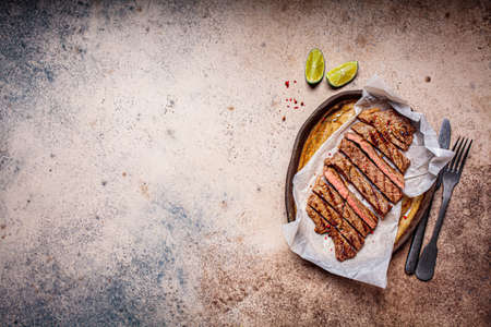 Sliced grilled beef steak with spices in a dark dish, dark background.