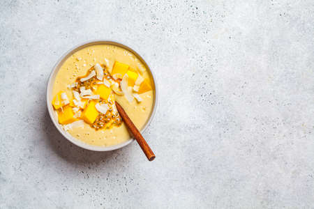 Tropical mango and coconut smoothie bowl, light background, copy space.