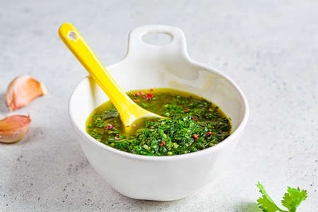 Fresh traditional chimichurri sauce for barbecue meat in a white bowl, light background.
