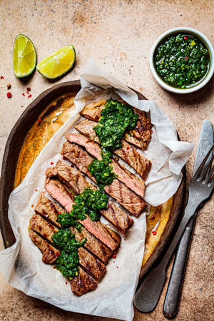 Sliced grilled beef steak with chimichurri sauce on a dark dish, dark background.