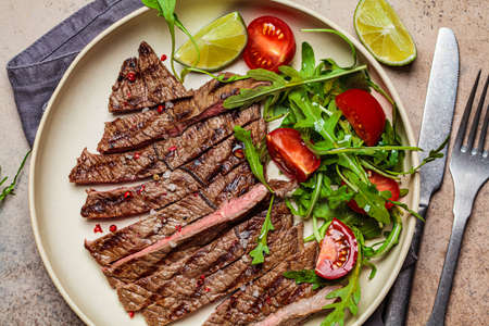 Sliced grilled beef steak with arugula and tomato salad in a white plate, dark background.