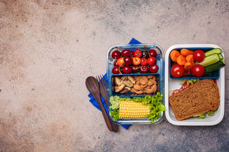 Lunch box with healthy fresh food. Sandwich, vegetables, fruits and nuts in food container, dark background.