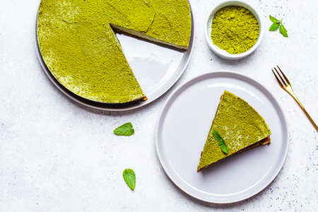 Raw vegan matcha cheesecake on a gray plate. Standard-Bild