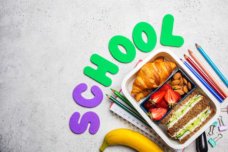 Back to school concept. Lunch box with a sandwich, croissants and snacks for school. School background with the inscription - school. Zdjęcie Seryjne