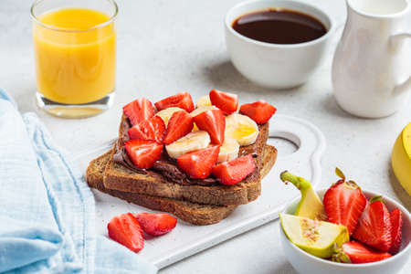 Toast with chocolate paste, banana and strawberries for breakfast.