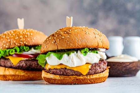 Homemade beef burgers with cheese, pickles and vegetables, gray background.