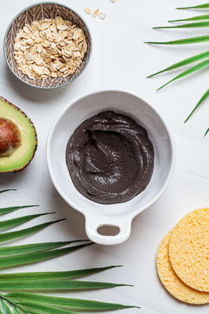 Cooking mask of black clay, avocado and oatmeal, white background. Skincare concept. Healthy skin.