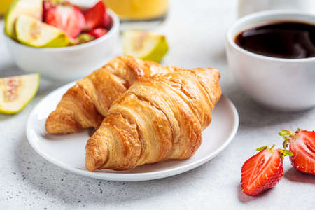 Breakfast croissants with coffee, juice and fruit, white background.