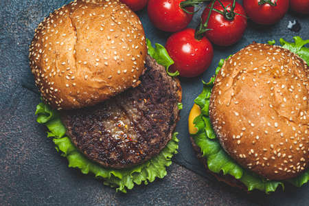 Homemade burgers with beef cutlet, cheese and vegetables, a dark background, top view. Zdjęcie Seryjne