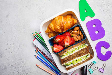 Back to school concept. Lunch box with a sandwich, croissants and snacks for school. School background with the inscription. Zdjęcie Seryjne