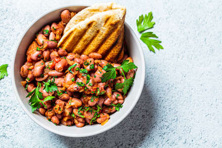 Stewed beans in tomato sauce with herbs and grilled tortillas. Vegetarian healthy food concept.