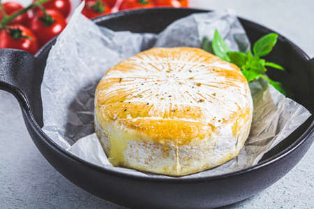 Baked Camembert or Brie cheese in a black pan.