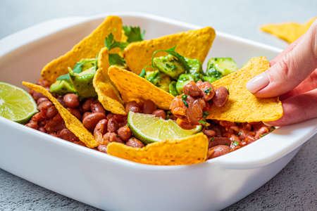 Bean salad with avocado and nachos in a white dish, gray background. Mexican food concept.