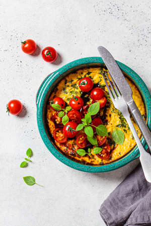 Baked egg omelet with tomatoes and basil, copy space. Breakfast concept. Standard-Bild