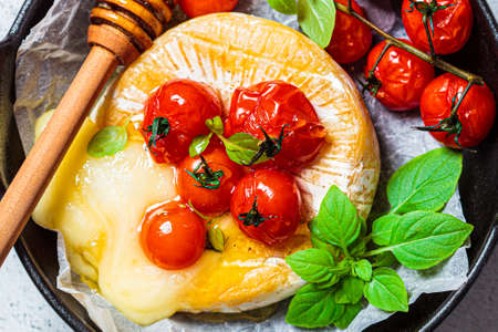 Baked Camembert or Brie cheese with tomatoes in a black pan.