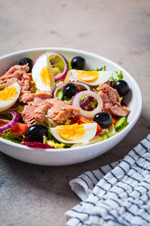 Tuna salad with egg, olives and vegetables in a white bowl, dark background. Diet food concept.