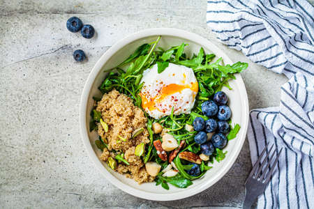 Vegetarian quinoa salad with poached egg and nuts. Healthy food concept. 스톡 콘텐츠