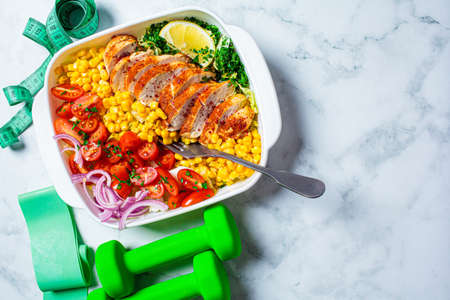 Fitness food concept. Diet chicken salad with vegetables in a white dish and sports tools on a white marble background.