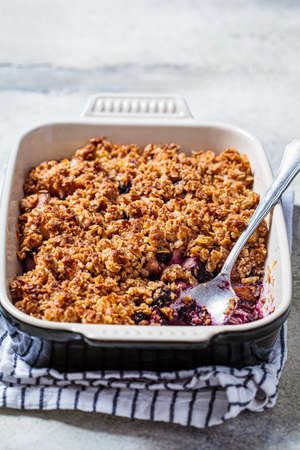 Homemade berry oat crumble pie in a backing dish. Comfort food concept.
