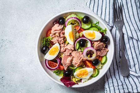 Tuna salad with egg, olives and vegetables in a white bowl, white background. Diet food concept.