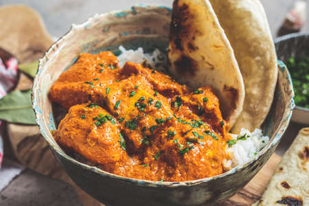 Chicken tikka masala in a spicy sauce with rice and chapati bread, dark background. Indian cuisine concept.