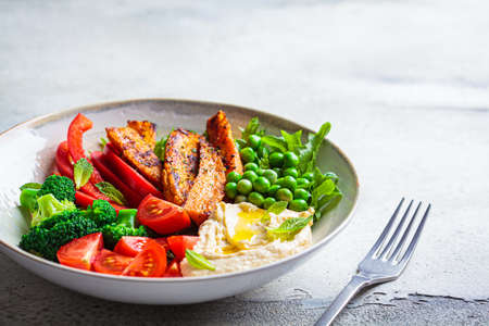 Vegan salad bowl with sweet potatoes, broccoli, tomato, peas and hummus. Healthy food concept.