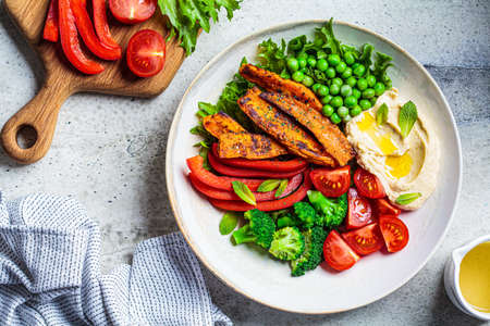 Vegan salad bowl with sweet potatoes, broccoli, tomato, peas and hummus, top view. 免版税图像